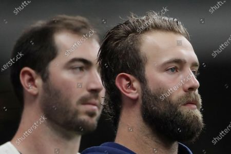 Milwaukee Brewers' Daniel Norris, right, and John Curtiss, left, stand for the National Anthem before a baseball game against the Pittsburgh Pirates, in Milwaukee