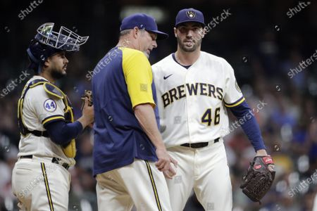 Stock Image of Milwaukee Brewers' John Curtiss (46) talks with pitching coach Chris Hook and Omar Narvaez during the seventh inning of a baseball game against the Pittsburgh Pirates, in Milwaukee