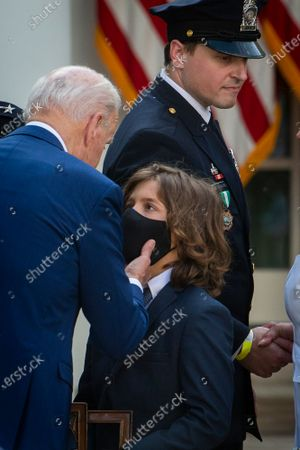 """United States President Joe Biden comforts Logan Evans, son of slain Capitol Police Officer William """"Billy"""" Evans, after signing H.R. 3325, """"An Act to award four Congressional gold medals to the United States Capitol Police and those who protected the U.S. Capitol,"""" into law in the Rose Garden of the White House in Washington, DC,."""