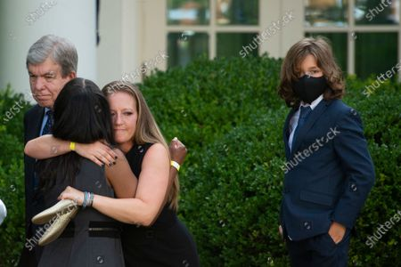 """Anne Winters, left, sister of USCP Officer Howard Liebengood gets a hug from Shannon Terranova, right, ex-wife of USCP Officer William """"Billy"""" Evans, as Logan Evans looks on at right, after United States President Joe Biden signed H.R. 3325, """"An Act to award four Congressional gold medals to the United States Capitol Police and those who protected the U.S. Capitol,"""" into law in the Rose Garden of the White House in Washington, DC,."""