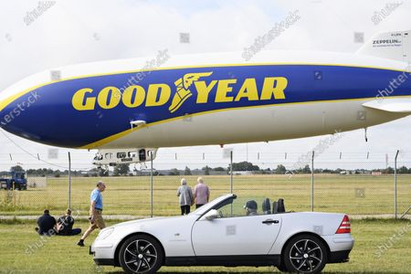 People look at the German zeppelin airship 'Goodyear Blimp' as it is fixed at Roskilde Airport, Denmark, 06 August 2021. The airship was supposed to fly trips with guests, but had to stays grounded due to the wind. The airship is 75 meters long, almost 20 meters wide and 18 meters high. The 'balloon' itself has a volume of 8425 cubic meters. The airship can fly at 125 kilometers per hour and at a maximum altitude of three kilometers.