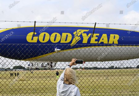 A person behind a fence takes a smartphone image of the German zeppelin airship 'Goodyear Blimp' as it is fixed at Roskilde Airport, Denmark, 06 August 2021. The airship was supposed to fly trips with guests, but had to stays grounded due to the wind. The airship is 75 meters long, almost 20 meters wide and 18 meters high. The 'balloon' itself has a volume of 8425 cubic meters. The airship can fly at 125 kilometers per hour and at a maximum altitude of three kilometers.