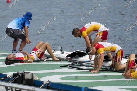 Marcus Walz, Rodrigo Germade, Carlos Arevalo and Saul Craviotto of Spain collapse on the dock after their silver medal finish in the men's kayak four 500m final at the 2020 Summer Olympics, in Tokyo, Japan