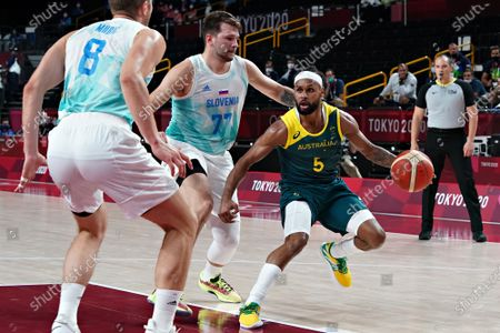 Australia point guard Patty Mills (5) drives to the basket past Slovenia point guard Luka Doncic (77) and forward Edo Muric (8), during the Men's Basketball bronze medal game at the Tokyo Olympic Games in Tokyo, Japan, on Saturday, August 7, 2021.