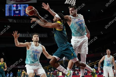 Australia's Patty Mills (5) passes off the ball against Slovenia's Mike Tobey (10) and Luka Doncic (77) during the men's bronze medal basketball game at the 2020 Summer Olympics, in Tokyo, Japan