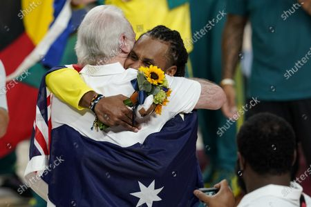 Australia's Patty Mills (5) hugs U.S. coach Gregg Popovich during the medal ceremony for basketball game at the 2020 Summer Olympics, in Tokyo, Japan
