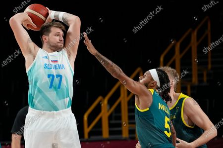 Slovenia's Luka Doncic (77) looks to pass over Australia's Patty Mills (5) during the men's bronze medal basketball game at the 2020 Summer Olympics, in Tokyo, Japan