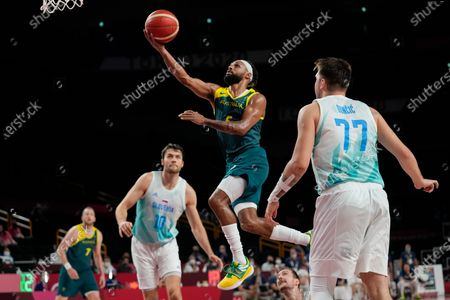 Australia's Patty Mills (5) puts up a shot against Slovenia's Luka Doncic (77) and Mike Tobey (10) during the men's bronze medal basketball game at the 2020 Summer Olympics, in Tokyo, Japan