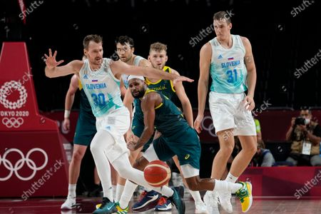 Australia's Patty Mills, center, strips the ball from Slovenia's Zoran Dragic (30) during the men's bronze medal basketball game at the 2020 Summer Olympics, in Tokyo, Japan