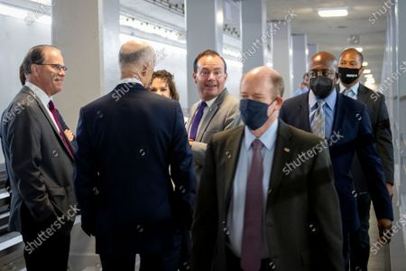 United States Senator Mike Lee (Republican of Utah), third from right, talks with United States Senator Mike Braun (Republican of Indiana), left, and United States Senator Rick Scott (Republican of Florida), second from left, as United States Senator Chris Coons (Democrat of Delaware), second from right, and United States Senator Raphael G. Warnock (Democrat of Georgia), right, pass by in the Senate subway tunnel at the US Capitol during a vote in Washington, DC,.