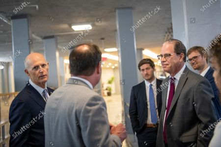 United States Senator Mike Lee (Republican of Utah), center, talks with United States Senator Mike Braun (Republican of Indiana), right, and United States Senator Rick Scott (Republican of Florida), left, in the Senate subway tunnel at the US Capitol during a vote in Washington, DC,.