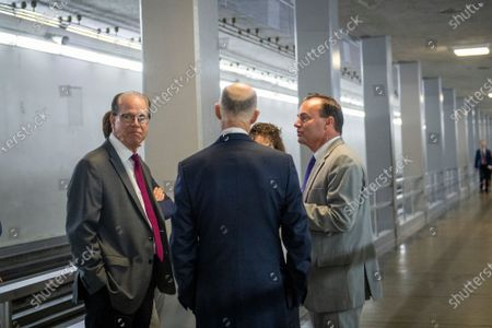United States Senator Mike Lee (Republican of Utah), right, talks with United States Senator Mike Braun (Republican of Indiana), left, and United States Senator Rick Scott (Republican of Florida), center, in the Senate subway tunnel at the US Capitol during a vote in Washington, DC,.