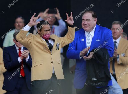 Class of 2020 inductee, Troy Polamalu, reacts after receiving his gold jacket from NFL Commissioner Roger Goodell and Hall of Fame president David Baker (R) during his enshrinement into the Pro Football Hall of Fame at Tom Benson Hall of Fame Stadium in Canton, Ohio on Saturday, August 7, 2021.