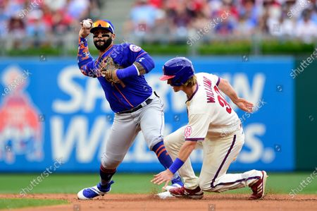 New York Mets' Jonathan Villar, left, turns a double play on a ball hit by Philadelphia Phillies' Zack Wheeler as Luke Williams, right, slides into second base during the fifth inning of a baseball game, in Philadelphia