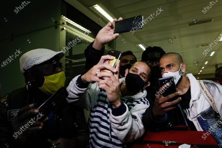 Daniel Alves, soccer player with Brazil's Olympic team that won the gold at the 2020 Tokyo Olympics, right, poses for photos with fans as he arrives to Sao Paulo International Airport in Guarulhos, Brazil