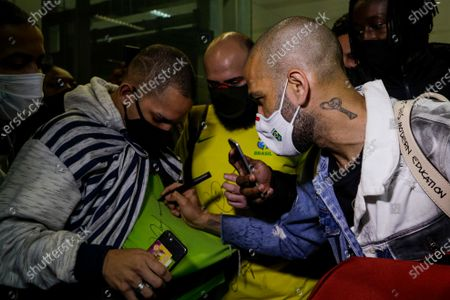 Daniel Alves, soccer player with Brazil's Olympic team that won the gold at the 2020 Tokyo Olympics, right, autographs a fan's shirt as he arrives to Sao Paulo International Airport in Guarulhos, Brazil