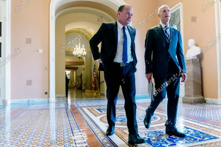 Sen. Mike Lee, R-Utah, left, and Sen. Rick Scott, R-Fla., right, walk out of a meeting in the office of Senate Minority Leader Mitch McConnell of Ky. as the $1 trillion bipartisan infrastructure bill gets closer to passage in Washington