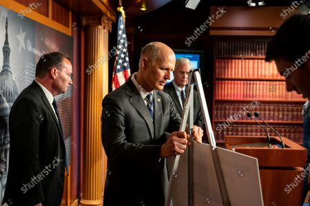 Sen. Rick Scott (R-FL), center, adjusts a visual aid before starting a news conference with Sen. Mike Lee (R-UT) and Sen. Ron Johnson (R-WI) on Capitol Hill on Monday, Aug. 9, 2021 in Washington, DC. The Senate, in final debate, prepares to vote on a $1 trillion bipartisan infrastructure bill. (Kent Nishimura / Los Angeles Times)