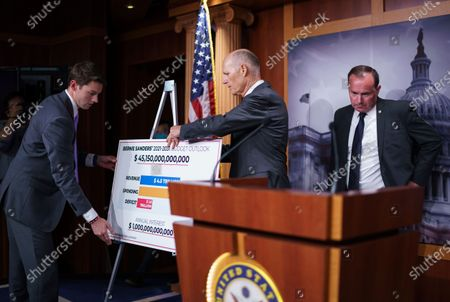 Sen. Rick Scott, R-Fla., center, joined at right by Sen. Mike Lee, R-Utah, sets up a poster as he charges Sen. Bernie Sanders, I-Vt., chair of the Senate Budget Committee, with contributing to inflation, during a news conference at the Capitol in Washington