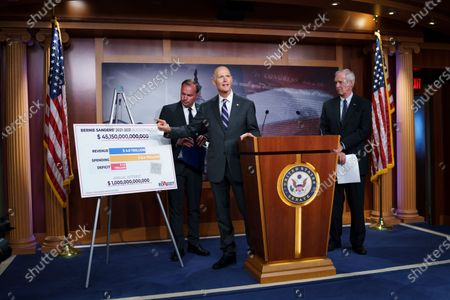 Sen. Rick Scott, R-Fla., flanked by Sen. Mike Lee, R-Utah, left, and Sen. Ron Johnson, R-Wis., charges Sen. Bernie Sanders, I-Vt., chair of the Senate Budget Committee, with contributing to inflation, during a news conference at the Capitol in Washington