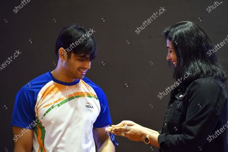 Stock Image of Neeraj Chopra, who won the gold medal in the javelin throw event of the recently concluded Tokyo Olympics 2020, looks at his medal along with former athlete Anju Bobby George during a press conference   on August 10, 2021 in New Delhi, India.