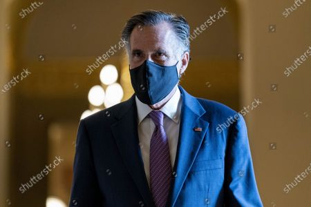 Sen. Mitt Romney, R-Utah, walks towards the chamber as the Senate moves from passage of the infrastructure bill to focus on a massive $3.5 trillion budget resolution, a blueprint of President Joe Biden's top domestic policy ambitions, at the Capitol in Washington