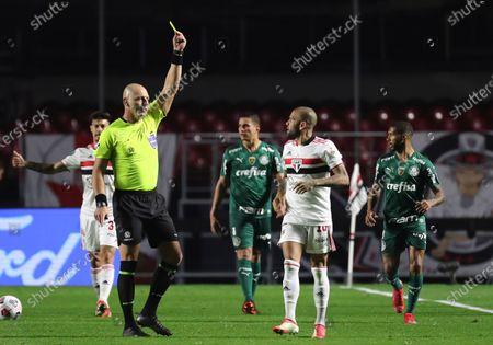 Referee Nestor Pitana shows the yellow card to Daniel Alves of Brazil's Sao Paulo during a Copa Libertadores soccer match against Brazil's Palmeiras at Morumbi stadium in Sao Paulo, Brazil, Tuesday, Aug.10, 2021