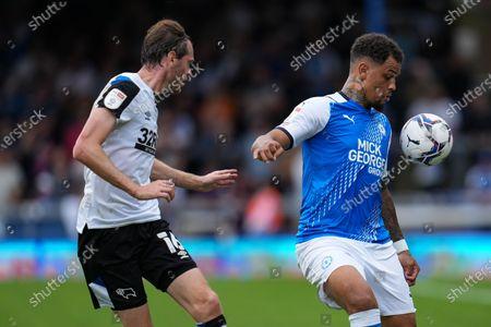 Richard Stearman of Derby County (16) and Jonson Clarke-Harris of Peterborough United (9)