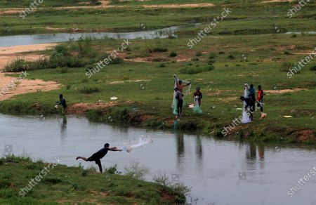 Stock Picture of Local villager are seen on the banks of river Daya as they throws their fishing nets into the flash flood water to catch fishes just outskirts of the eastern Indian state Odisha's capital city Bhubaneswar, India, on August 11, 2021