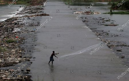 Local villager are seen on the banks of river Daya as they throws their fishing nets into the flash flood water to catch fishes just outskirts of the eastern Indian state Odisha's capital city Bhubaneswar, India, on August 11, 2021