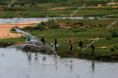 Stock Image of Local villager are seen on the banks of river Daya as they throws their fishing nets into the flash flood water to catch fishes just outskirts of the eastern Indian state Odisha's capital city Bhubaneswar, India, on August 11, 2021