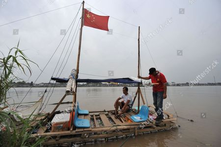 Xia Yu (red t-shirt) and a friend complete the bottle boat's 1,500km journey. Shanghai, China.