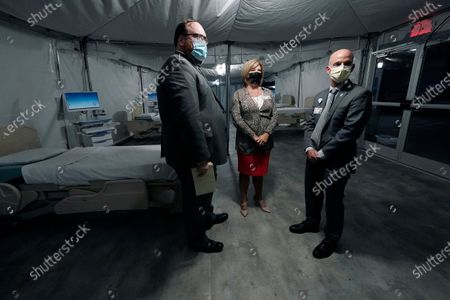University of Mississippi Medical Center's Dr. LouAnn Woodward, vice chancellor for health affairs and dean of the School of Medicine, center, stands with Jonathan Wilson, chief administrative officer, left, and Dr. Alan Jones, associate vice chancellor for clinical affairs, as they wait for the start of a news conference and walk-thru of a COVID-19 mobile field hospital erected in a parking garage at the Medical Center in Jackson, Miss., . The temporary facility will be partially staffed with members of a on-site clinical team from the National Disaster Medical System. The field unit has a mixture of inpatient and outpatient services and will serve as a resource for the entire state, not just UMMC