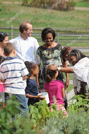 United States First Lady Michelle Obama and chef Dan Barber speak with children working in the herb garden. Also visible in the photo is Elisabeth Preval of Haiti at right