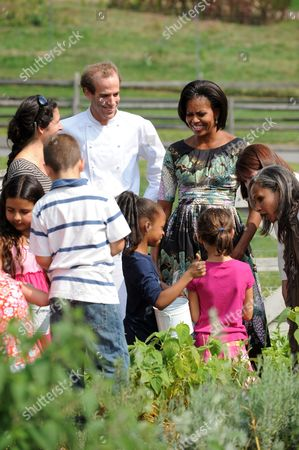 United States First Lady Michelle Obama and chef Dan Barber speak with children working in the herb garden