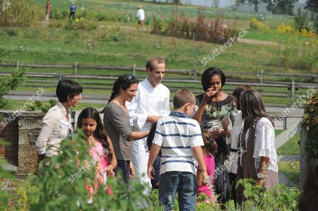 Stock Picture of United States First Lady Michelle Obama and chef Dan Barber speak with children working in the herb garden. Also visible in the photo is Elisabeth Preval of Haiti at right