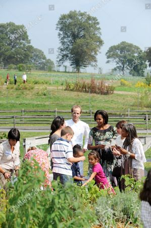 United States First Lady Michelle Obama and chef Dan Barber speak with children working in the herb garden Also visible in the photo is Elisabeth Preval of Haiti at right