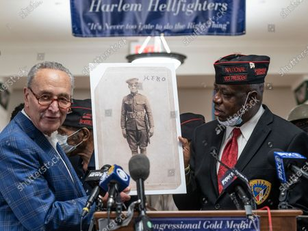 Senator Chuck Schumer, elected officials honor members of 369th Regiment and The Harlem Hellfighters and Harlem Armory. Senator Schumer annonced Congressional Gold Medal awarded to Harlem Hellfighters and presented The Legion of Merit Award from the US Senate to Command Sergeant Major Andrew Lampkins. Schumer was joined by elected officials U.S. Representatives Tom Suozzi and Adriano Espaillat, former U.S. Representative Charles Rangel, NYS Senator Brian Benjamin, NYS Assemblymembers Inez Dickens and Al Taylor, as well as family members of the Harlem Hellfighters. In this photo Senator Schumer, Vice President of 369th Regiment Veterans Association Charles Hall holding photo of member of Harlem Hellfighters.