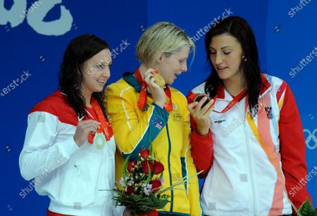 Australia's gold medal winner Leisel Jones looks at the bronze medal of Austria's Mirna Jukic (R) as silver medalist USA's Rebecca Soni (L) looks on during the awards ceremony for the Women's 100N Breaststroke at the National Aquatics Center at the Summer Olympics in Beijing on August 12, 2008.  Jones set an Olympic Record with 1:05.17.