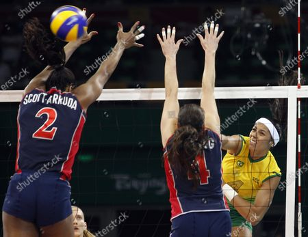 Brazil's Paula Pequeno's (R) spikes a shot past USA's defenders Danielle Scott-Arruda (L) and Lindsey Berg in the women's volleyball final during the Beijing 2008 Olympic Games August 23, 2008. Brazil won the match 3-1, taking the gold, while USA settled for silver and China the bronze.