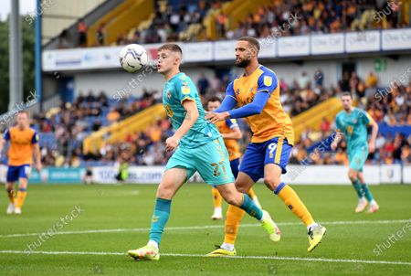 Lewis Collins of Newport County is tackled ny Jordan Bowery of Mansfield Town.