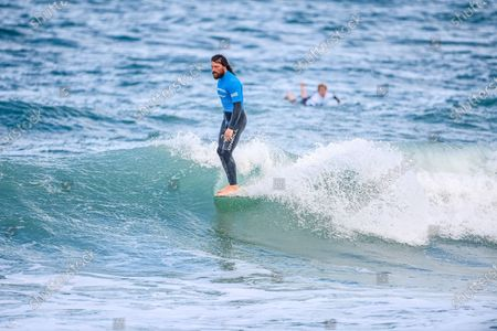 Wide view of Ben Skinner 'hanging ten' during the BF Goodrich Longboard Open at the Boardmasters Surfing Championship 2021 at Fistral Beach, Newquay