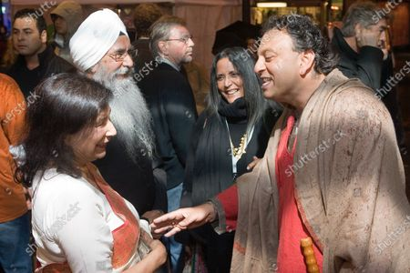 """A friend of writer/director Deepa Mehta talks to local actors Balinder Johal (L) and Rajinder Singh Cheema (beard) as they arrive at the Empire Granville 7 Theater to introduce their latest film """"Heaven on Earth"""" screening at the Vancouver International Film Festival in Vancouver, British Columbia, October 4, 2008."""