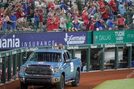 Retired player Adrian Beltre sits in the back of a truck while waving to fans as he is introduced during a ceremony before a baseball game between the Oakland Athletics and the Texas Rangers in Arlington, Texas, . Beltre and public address announcer Chuck Morgan were inducted into the Rangers' Hall of Fame on Saturday