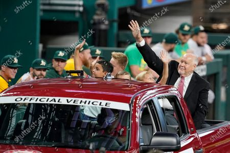 Texas Rangers public address announcer Chuck Morgan waves to fans from the back of a truck while passing the Oakland Athletics dugout during a ceremony before a baseball game in Arlington, Texas, . Retired player Adrian Beltre and Morgan were inducted into the Rangers' Hall of Fame on Saturday