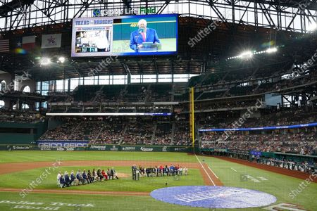 Texas Rangers public address announcer Chuck Morgan stands at a lectern and is displayed on-screen as he speaks during a ceremony before a baseball game against the Oakland Athletics in Arlington, Texas, . Morgan and retired player Adrian Beltre were inducted into the Rangers' Hall of Fame on Saturday