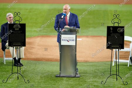 Texas Rangers public address announcer Chuck Morgan, center, speaks as team owner Ray Davis, left rear, looks on during a ceremony before a baseball game against the Oakland Athletics in Arlington, Texas, . Morgan and retired player Adrian Beltre and Morgan were inducted into the Rangers' Hall of Fame on Saturday