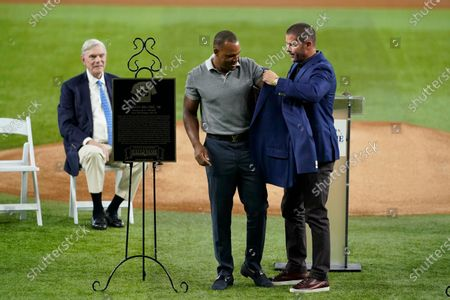 Former Texas Rangers player Adrian Beltre, center, is helped into his jacket by retired player Michael Young, right, as team owner Ray Davis, left rear, looks on during a ceremony before a baseball game against the Oakland Athletics in Arlington, Texas, . Beltre and team public address announcer Chuck Morgan were inducted into the Rangers' Hall of Fame on Saturday