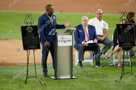 Retired Texas Rangers player Adrian Beltre, left, speaks as team public address announcer Chuck Morgan, center rear, looks on during a ceremony before a baseball game against the Oakland Athletics in Arlington, Texas, . Beltre and Morgan were inducted into the Rangers' Hall of Fame on Saturday