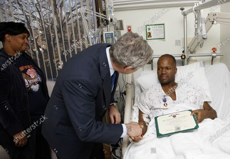 President George W. Bush shakes the hand of U.S. Army Sgt. First Class Neal Boyd of Haynesville, Louisiana, after presenting him a Purple Heart during a visit on December 22, 2008, to  Walter Reed Army Medical Center in Washington D.C., where the soldier is recovering from injuries received in the War in Iraq.  Looking on is SFC Boyd's wife, Joyce.